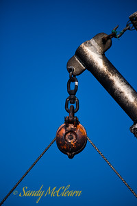 A pulley on a loading derrick on a fishing wharf.