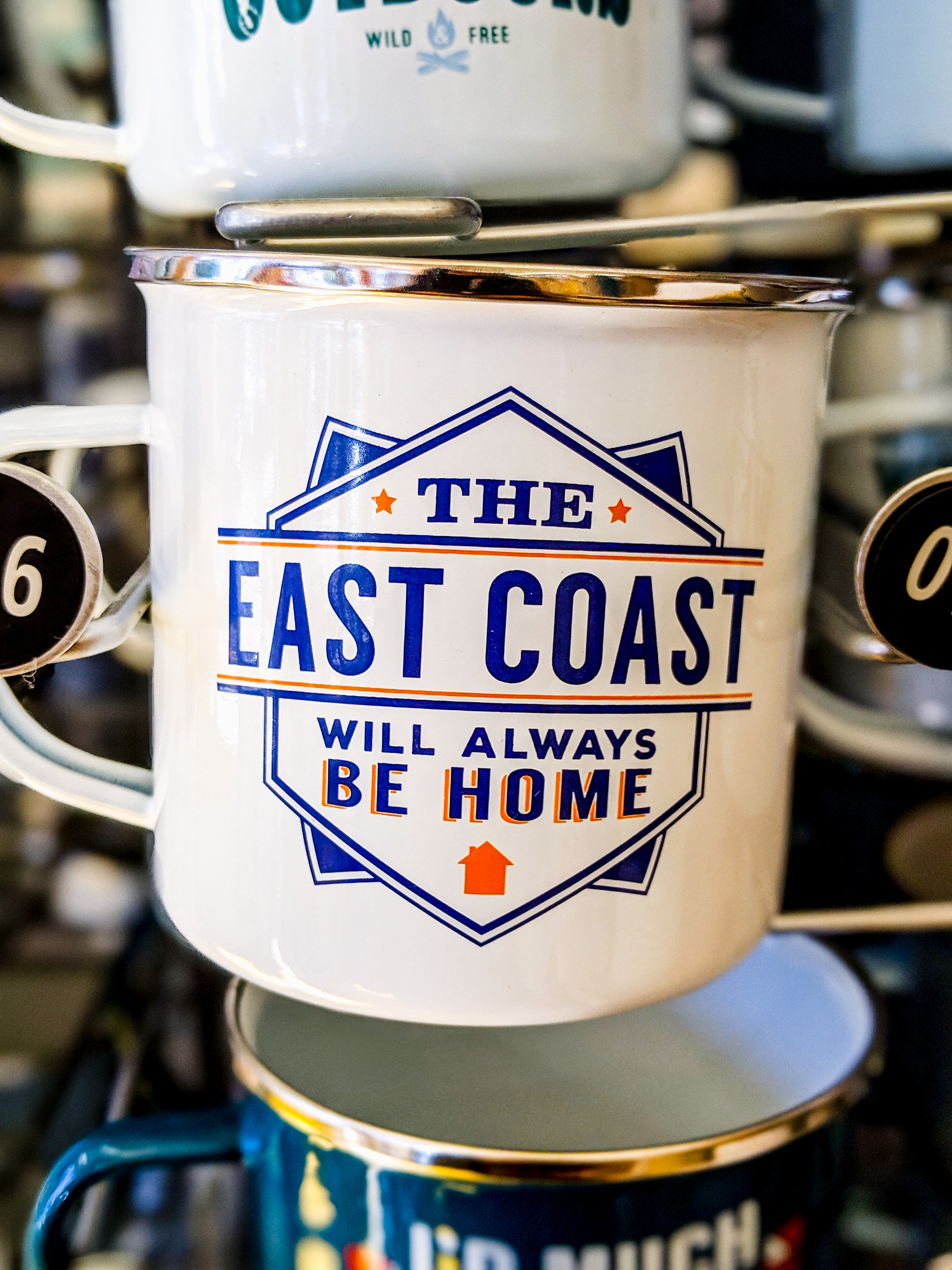 White camping mug that says The East Coast Will Always Be Home, found in a store in Annapolis Royal Nova Scotia