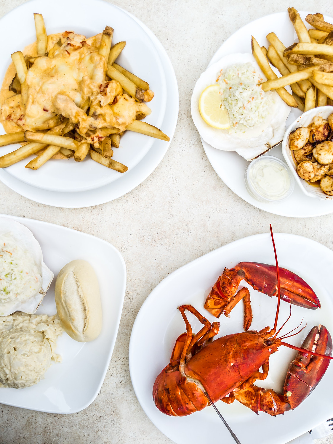 Halls Harbour Lobster Pound table with steamed lobster, scallops and lobster poutine.