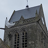 Church at St. Mere Eglise:  statue and parachute commemorate airman who landed on the tower of the church