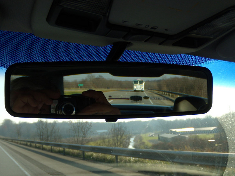 Firetruck now in my rear view mirror---now you see it is a BRAND NEW truck, since plastic covering in front. Probably made at the Columbus, Ohio Firetruck assembly plant.