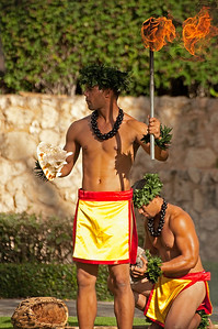 Two male Hawaiian dancers performing with fire torches and conch shells.