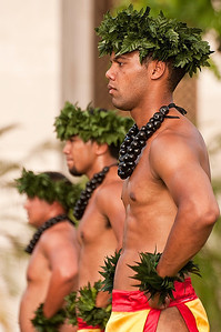 Three male Hawaiian dancers getting ready for the start of their dance performance in Oahu.