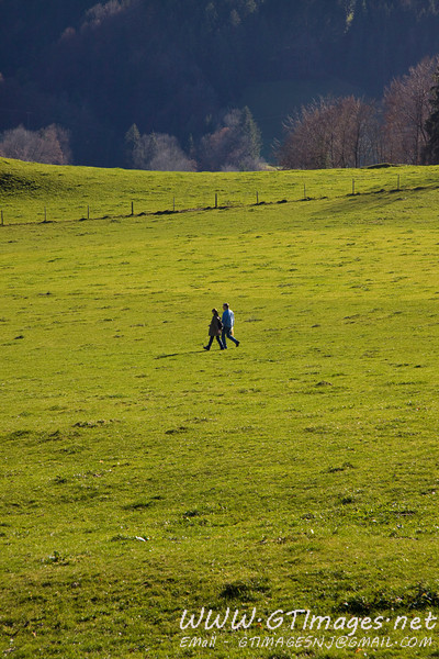 Two people walking across a meadow, in Oberstaufen.