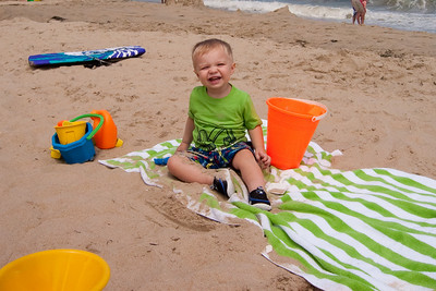 Ethan relaxes on the beach towel.