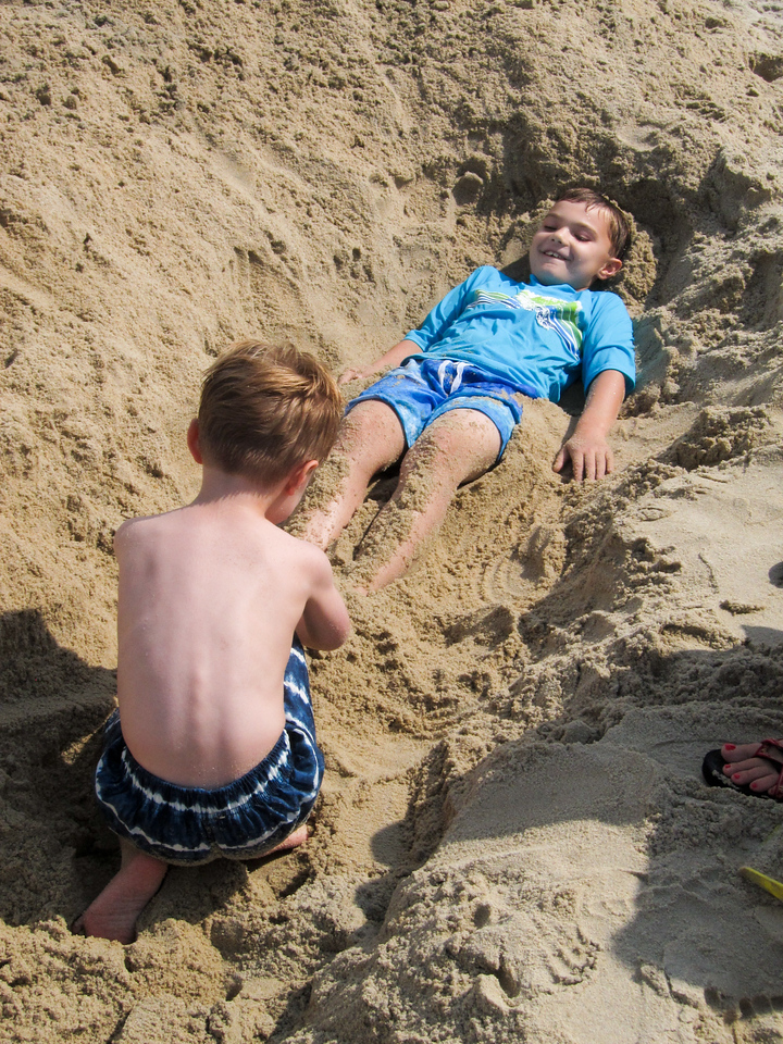 K.C. and Ethan play in a sand fort.