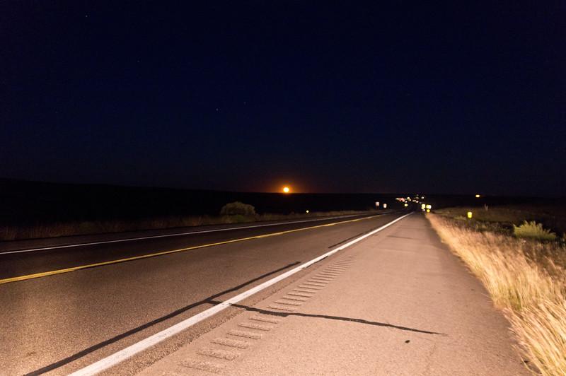 Moon rising over US 82 near Hope, NM