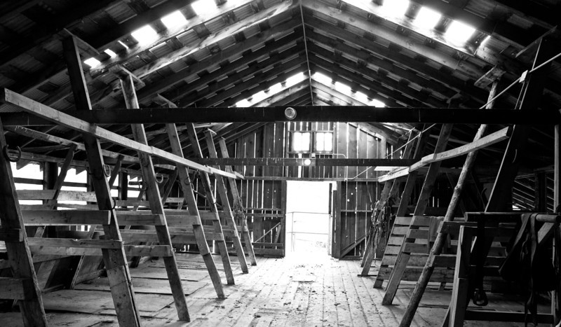 The interior of a barn with stables. Angles and light direction create ambiance. Estes Park, Colorado