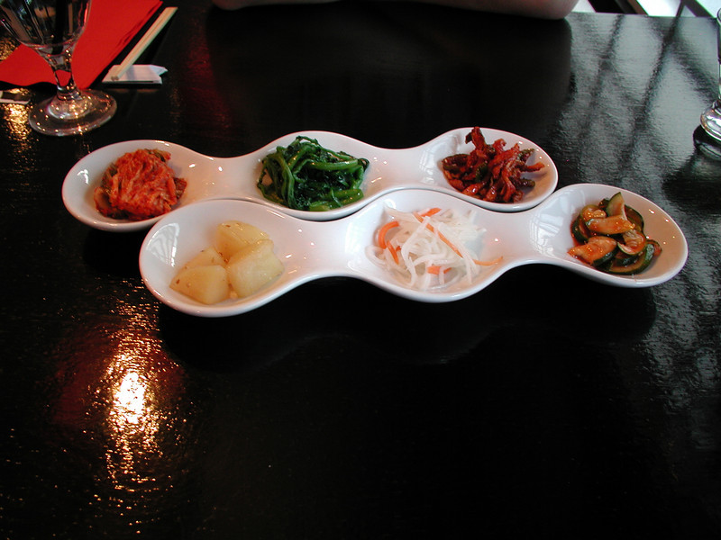 Clockwise from top left: Kimchee, watercress, radish with kimchee and chili flakes, sweet and sour cucumber, daikon with carrot, and potato. Sung Korean Bistro. Meeting Hai in Cincinnati, 4/16