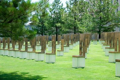 The glass base of each bronze and stone chair is etched with the name of a victim. The chairs are in two sizes.  The nineteen smaller chairs represent children.
