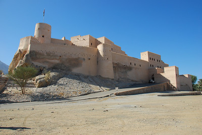 Nakhal Fort, Oman.  Its original construction pre-dates the arrival of Islam in Oman. The fort is built on top of a rock outcrop, parts of which are visible inside the fort. The towers and entrance way were built in the 1830s.