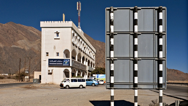 Commercial building and road sign, along the road to Nizwa.