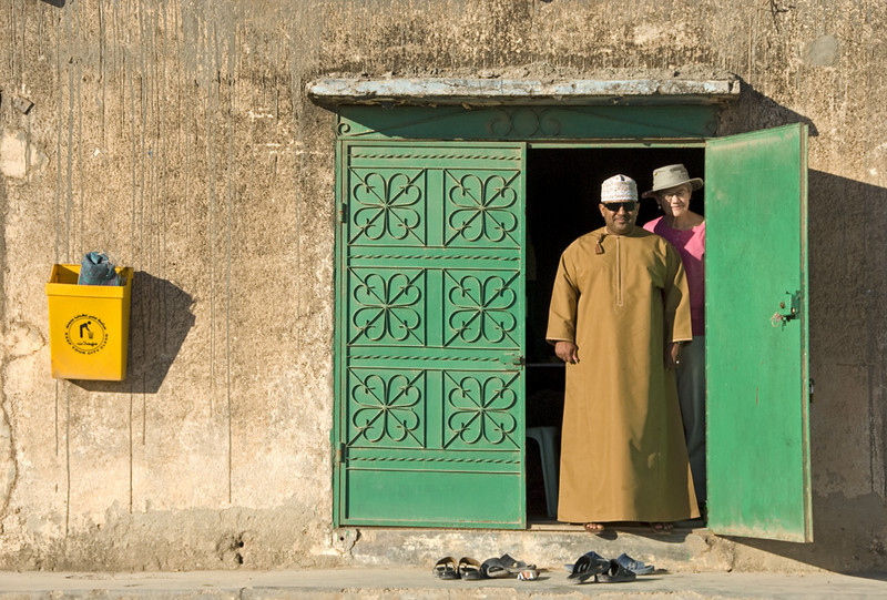 Khalid, our family guide in Salalah, and Carolyn, in the doorway of a restaurant in Sarfait.