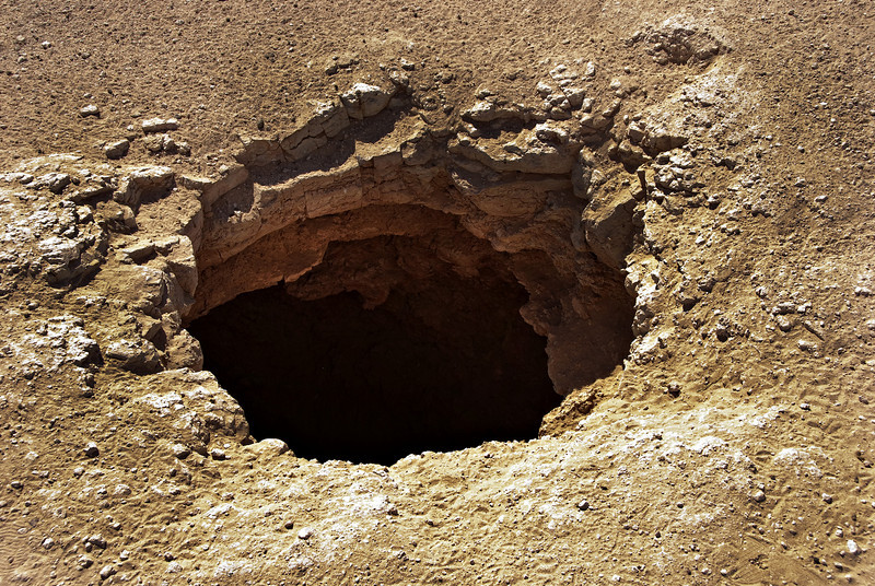 Impact hole, about three feet in diameter, of a recent meteorite strike near Thumrayt.