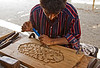 Wood carver at a boatyard, Sur.