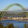 Yaquina Bay bridge: The structure is a combination of both steel and concrete arches. The main span of the 3,223-feet structure is a 600-foot steel through arch flanked by two 350-foot steel deck arches. There are five reinforced concrete deck arch secondary spans on the south end of the steel arches and fifteen concrete deck girder approach spans. Decorative elements include ornamental spandrel deck railing brackets, fluted entrance pylons, and a pedestrian plaza with elaborate stairways leading to observation areas.