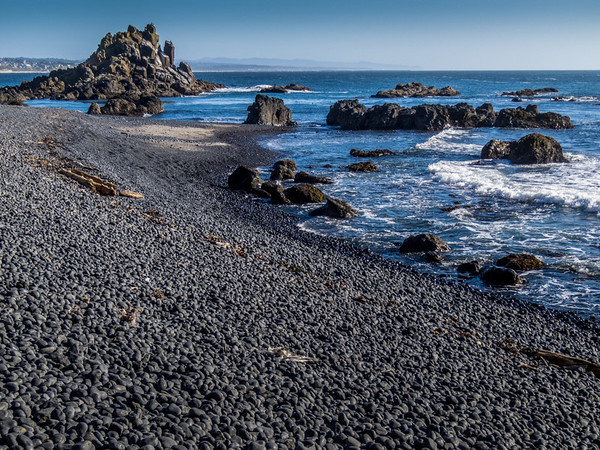 Black Pebble Beach located just below the Yaquina Head lighthouse.  Seabirds rest on the rock formations.  The city of Newport can be seen in the distance.