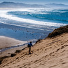 A hiker heads up the steep, sandy bluff at Cape Kiwanda.  Birds and people play along the beach below.