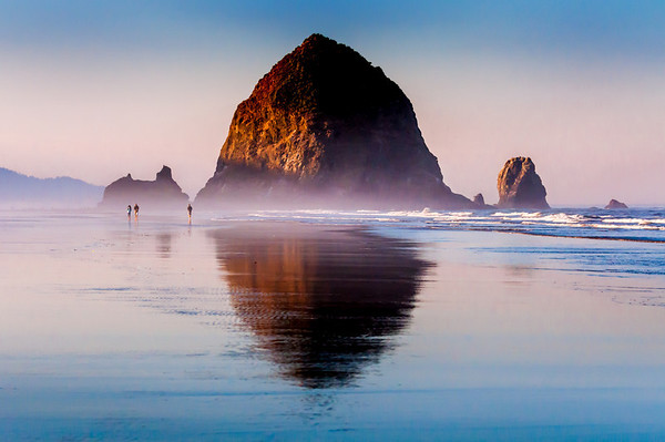 A few people walk along the beach in the early morning at low tide toward Haystack Rock at Cannon Beach.  A layer of fog still sits along the beach while sunlight begins to peak through and light up the rock.