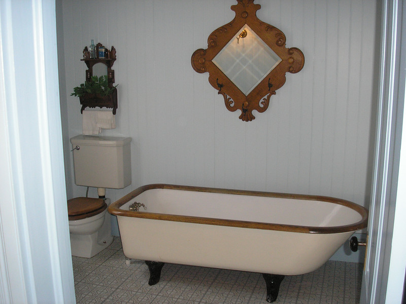 Cast iron clawfooted oak trimmed bathtub,is original to the Hughes House. The house was designed by the architect with indore plumbing in1898!!
