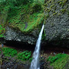 Ponytail Falls, one of many along the Columbia River Gorge historic highway.<br /> This feeds down to Horsetail Falls.  (Note people behind the falls.)<br /> September 6, 2009