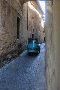 A narrow but vital street in Orvieto barely accomodates a motorized scooter.