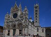 Siena Cathedral and its bell tower. Its horizontal striped theme is prominent inside.