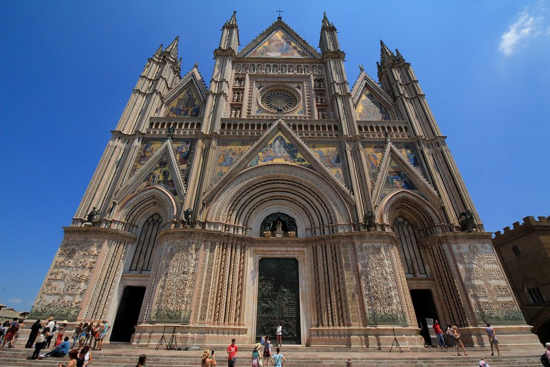 The colorful facade of the Orvieto Cathedral. In the days of ox carts, craftsmen and all materials had to be brought up a long and steep mountain slope to the site.