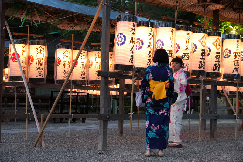 Two girls admire the lit lanterns at Yasaka shrine