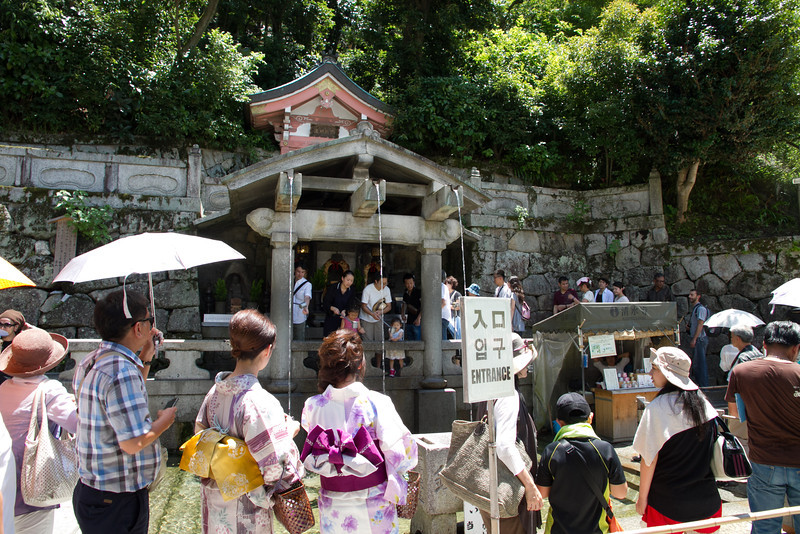 """Visitors line up to sample the waters from the temple (whose name means """"pure water"""")"""