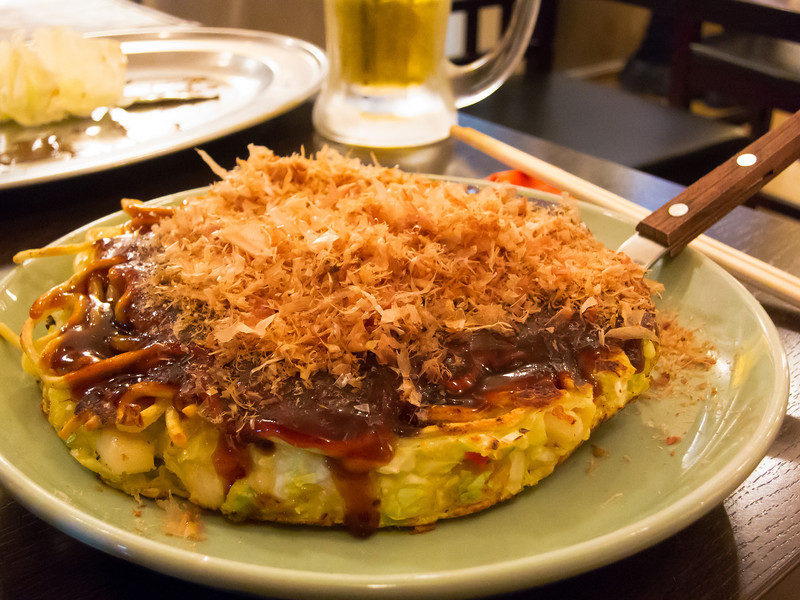 One of my favorite Japanese dishes, Okonomiyaki!  The Osaka-style has the cabbage mixed in with the pancake, while the Hiroshima-style is layered with the pancake, cabbage and meat seperated instead of mixed.  Honestly it all tasted the same to me but I think Hiroshima style is easier to eat.