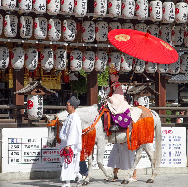 A boy chosen to represent a messenger from the gods is paraded past at Yasaka shrine