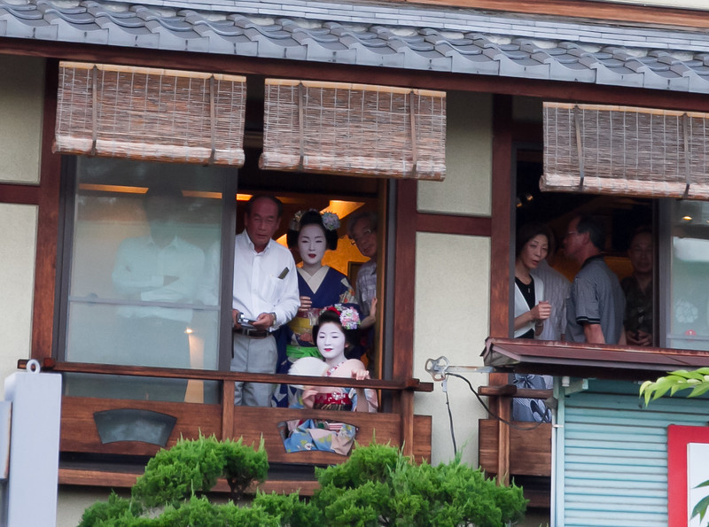 A party being entertained by geisha looks out the window at the festival below