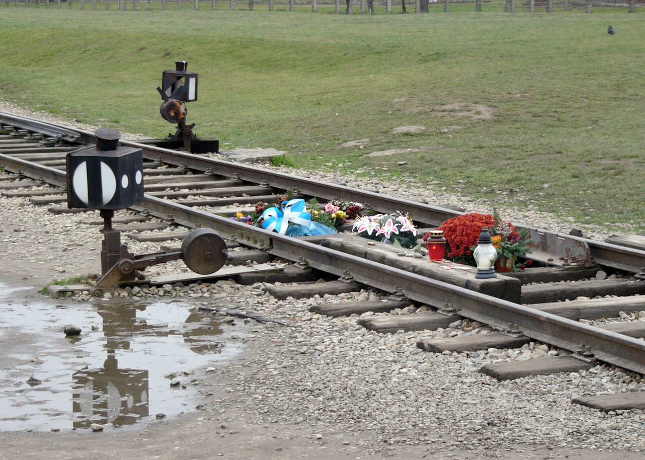 Flowers and candles left on train tracks at Auschwitz