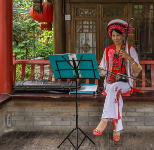 A musician playing a traditional Bai instrument at the hotel.  Notice her mostly white clothes