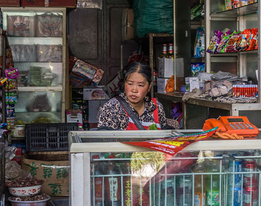 A shopkeeper in the market in Lijiang