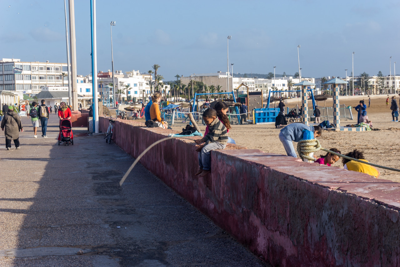 The beach area is filled with people late in the afternoon