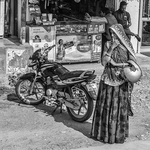 From the bus between Nagaur and Jaipur.  I wonder if the woman is holdling the helmut for a friend or if it is hers.