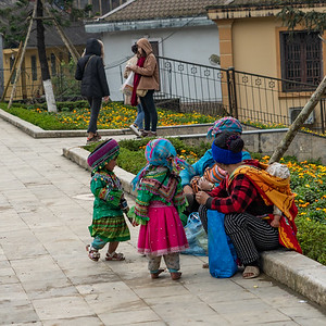 A family waiting to sell some handmade, embroided purses
