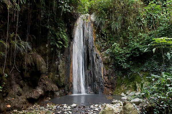 This waterfall is one outlet of water from a volcano and steam field. The rocks are colored from the iron oxide/hydroxide in the water and is black from precipitated metal sulfides (of copper, iron, and manganese).