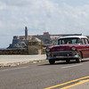 A classic driving along the Malecón with El Morro across the bay in the distance