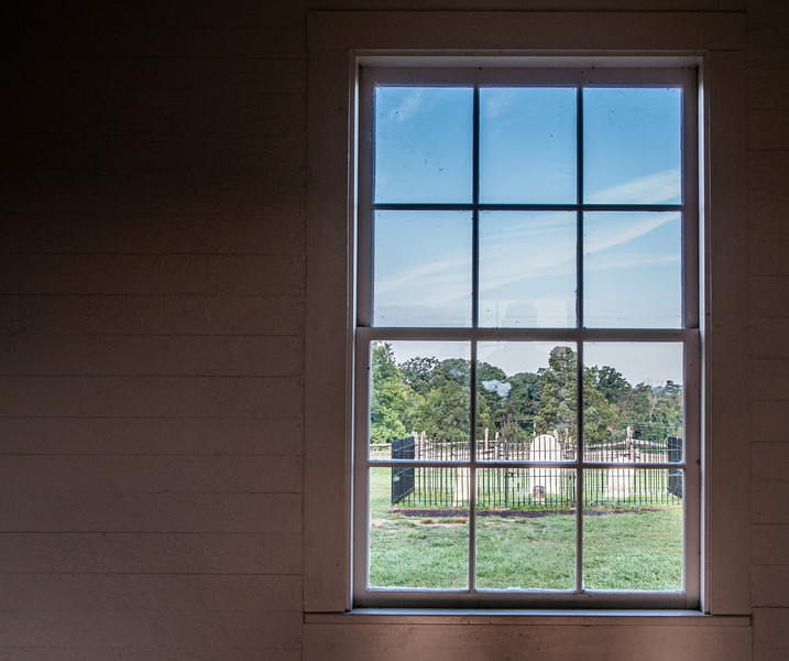 Looking out of the Stone House's window into a cemetery