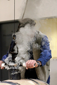 Durand disappears in a cloud of smoke as he burns out the hole where a large cork go.