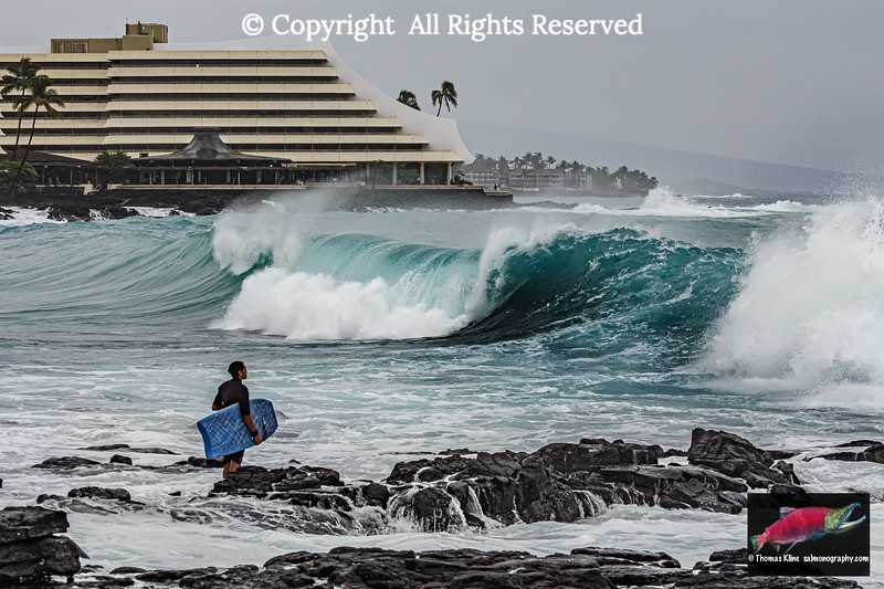Surfer observing large waves near Royal Kona Resort, Kailua-Kona, Hawaii Island