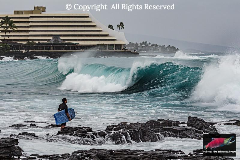 Surfer observing large waves near Royal Kona Resort, Kailua-Kona, Hawaii Island