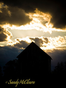 The sun peaks out from behind clouds with an old barn in the foreground.