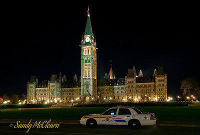 A police car sits in front of the Parliament Buildings.
