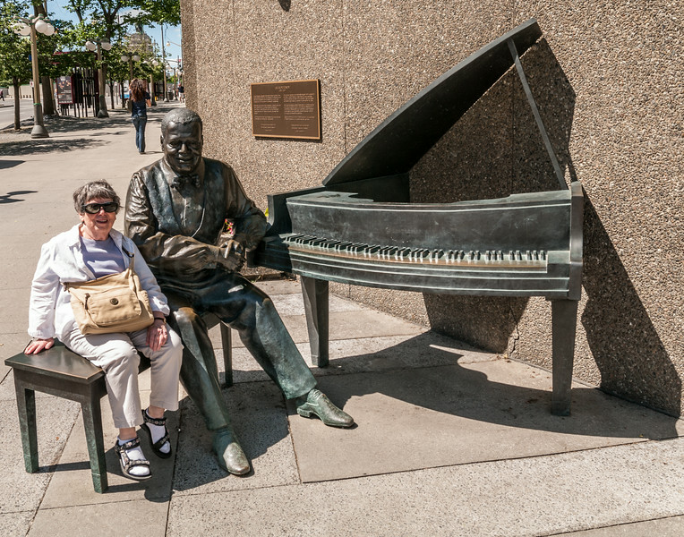 Leona sitting next to a statue and piano of Oscar Peterson