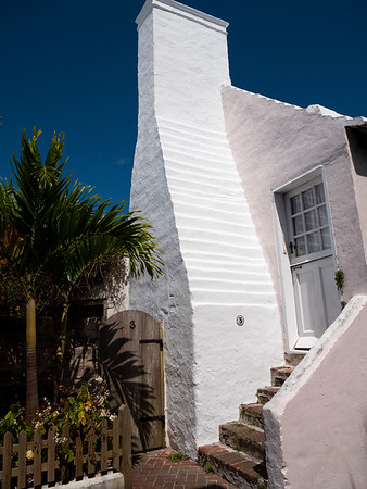 A humble cottage. The terraced rooves have become an emblematic design element, seen here in the sculpting of the chimney. The address is No. 3.