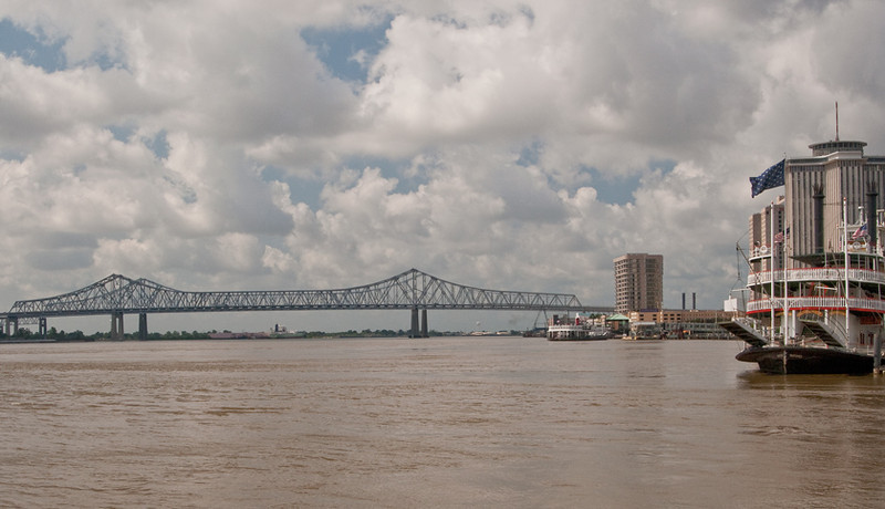 The greater New Orleans Bridge overshadowed by a bustling city, the Algiers ferry, and the sternwheeler Natchez.